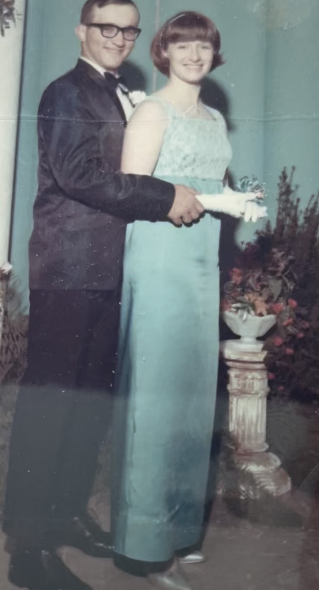 Boy and girl in senior prom photo, girl wearing long blue dress with laced bodice, boy in tuxedo about 1967
