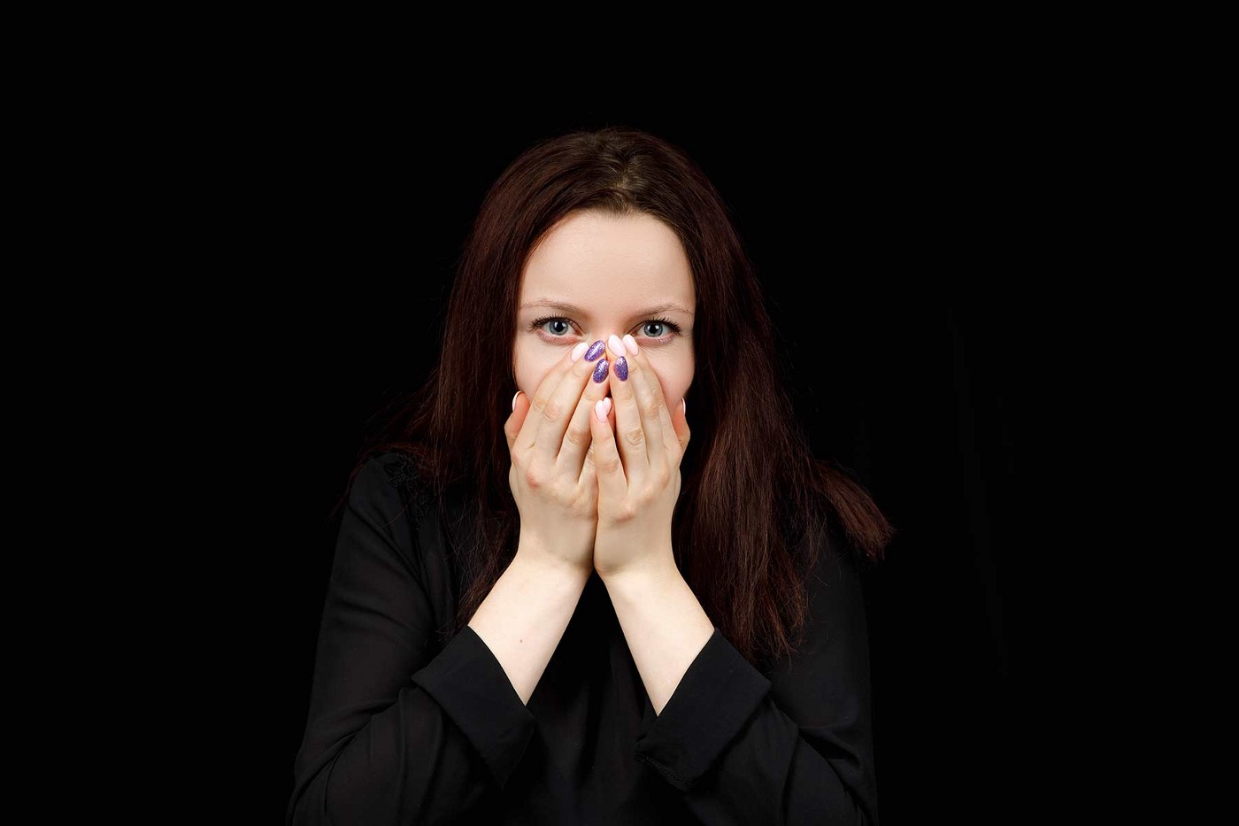A woman covers her mouth and nose with her hands. Here eyes convey a slight level of shock.