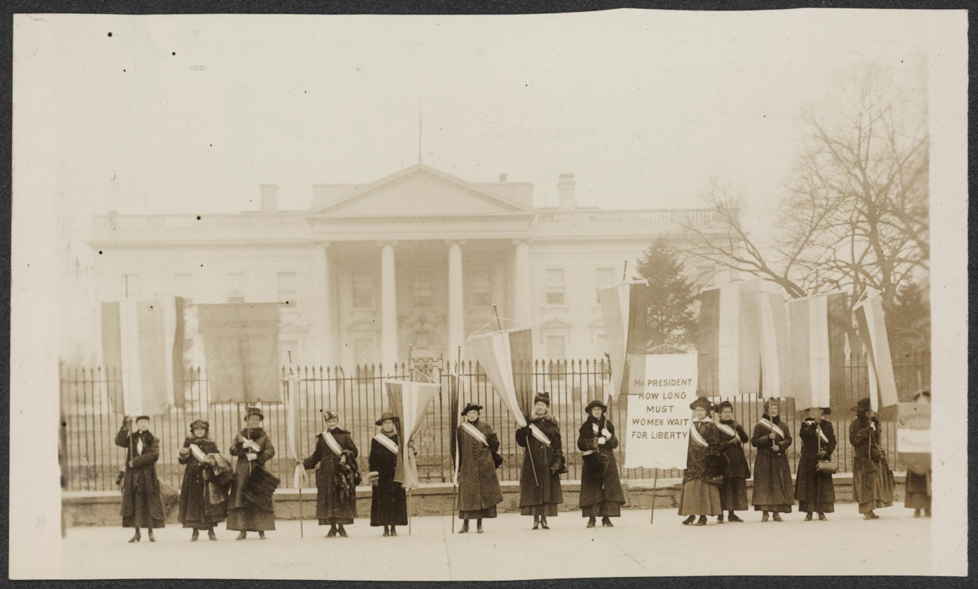 Women's suffragists hold banners in front of the White House gate, 1917