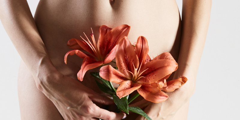 Woman with flowers in front of her private parts—5 Best Ways To Prepare For Oral Sex (For Women and Men)