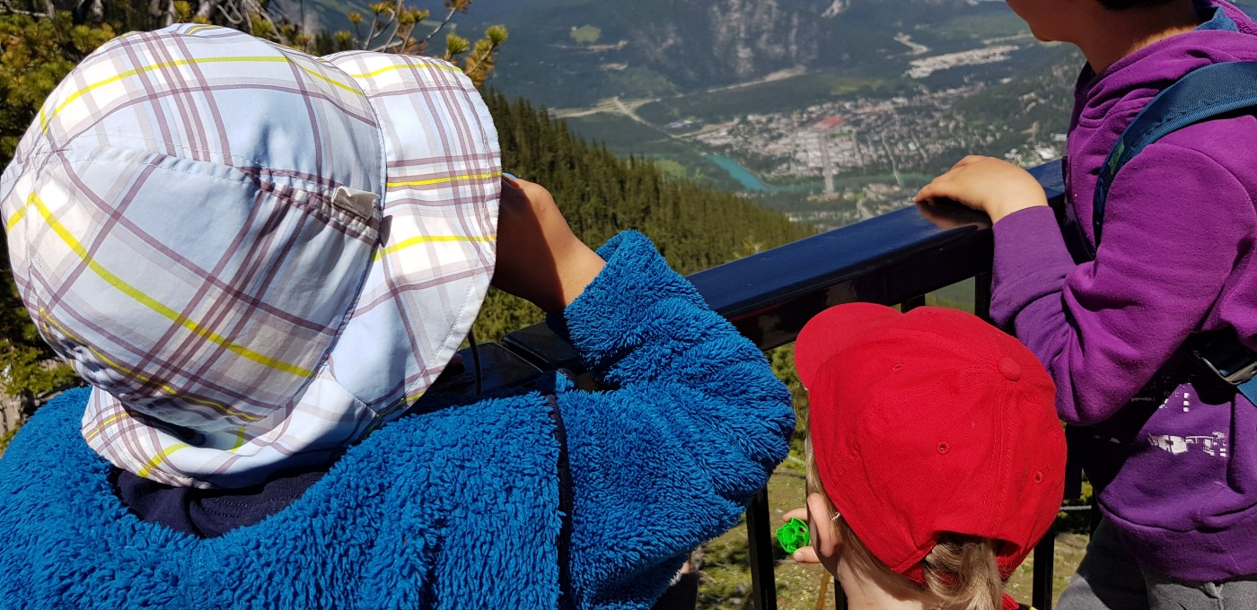 Three children looking down at a valley from a mountain lookout.