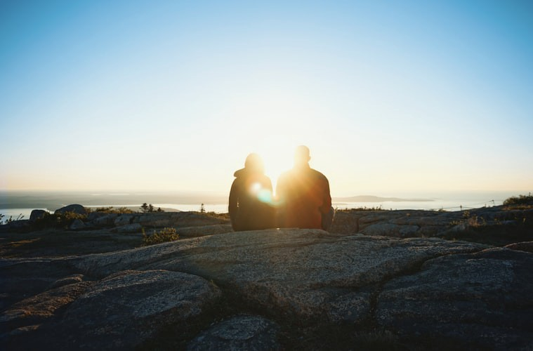 A couple sitting on a rock watching the sunrise