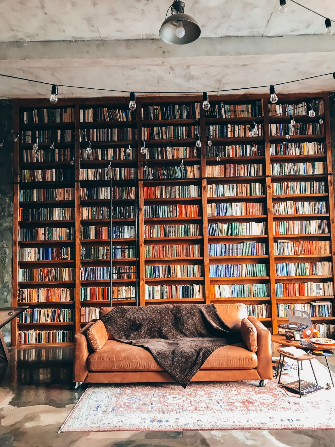 A large colorful bookcase fills an entire wall as an empty sofa beckons a reader to sit down.