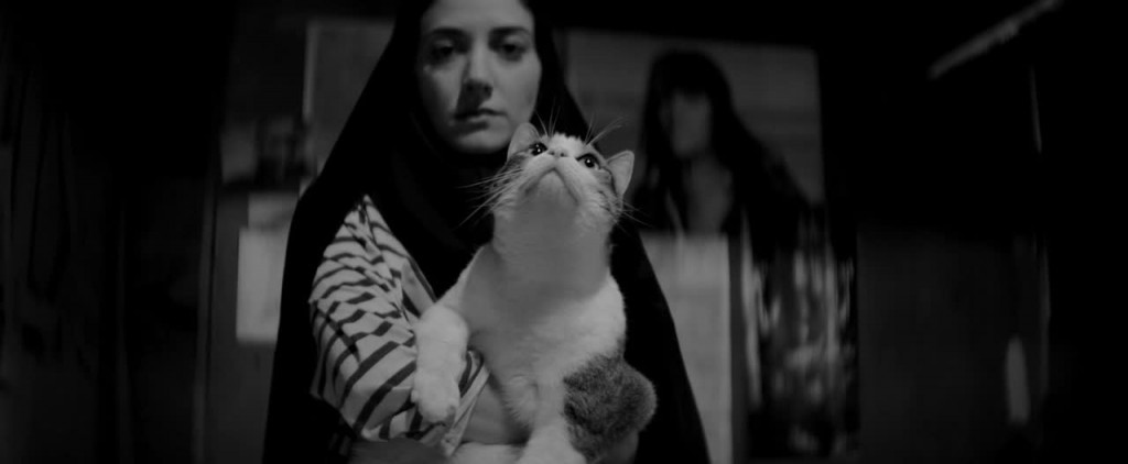 A female vampire wearing a chador holds a cat to the camera.