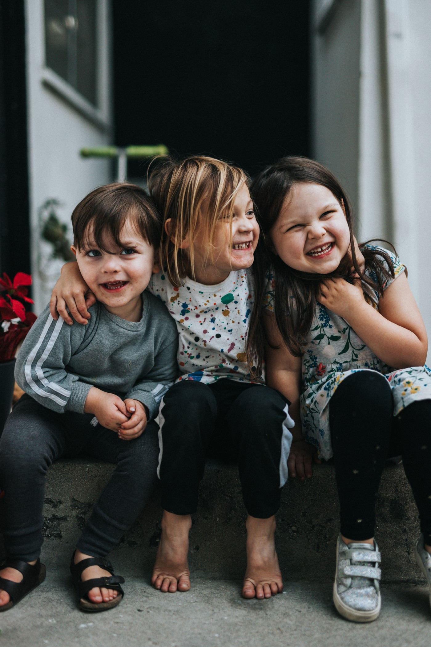 Three children smiling and hugging: two girls and a boy.