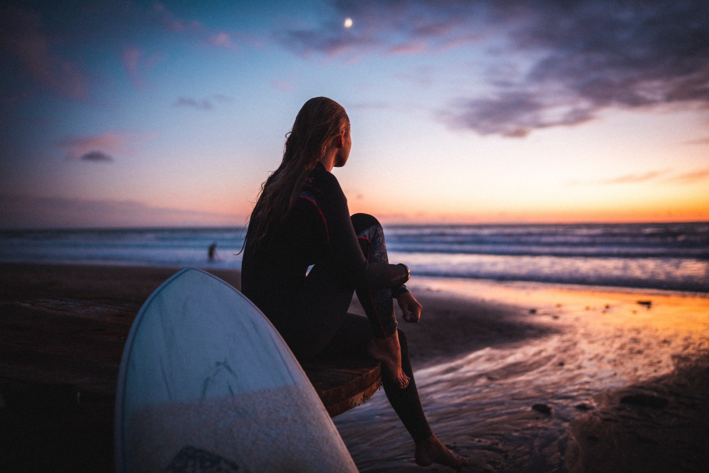 Woman in black jacket sitting on white surfboard on beach during sunset
