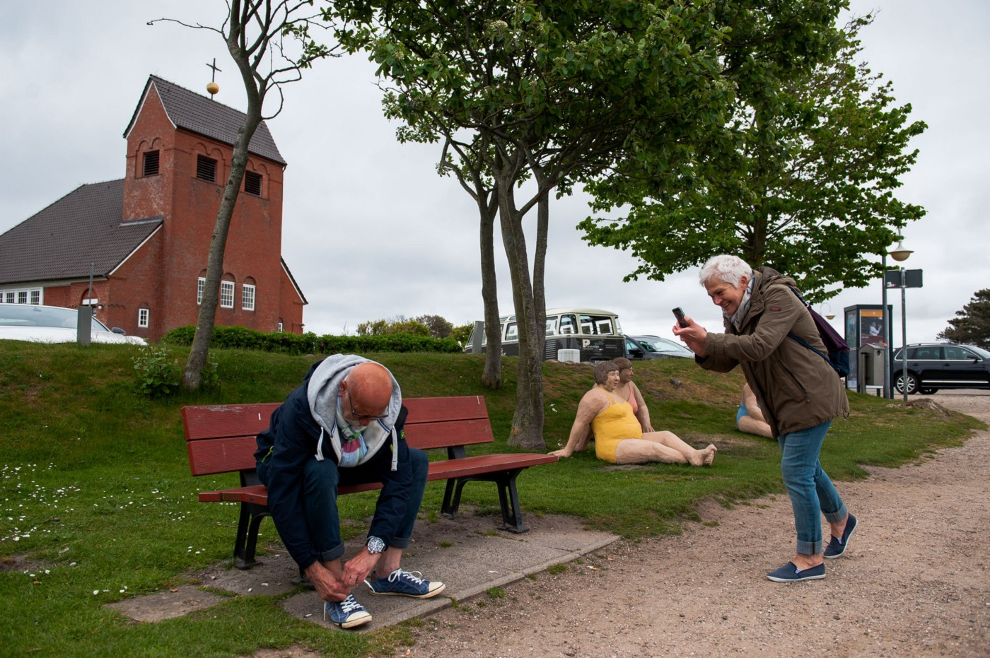 Having reached the pond in Wenningstedt, mom photographs dad fastening his shoelaces. Sylt, Germany, May 25, 2019.