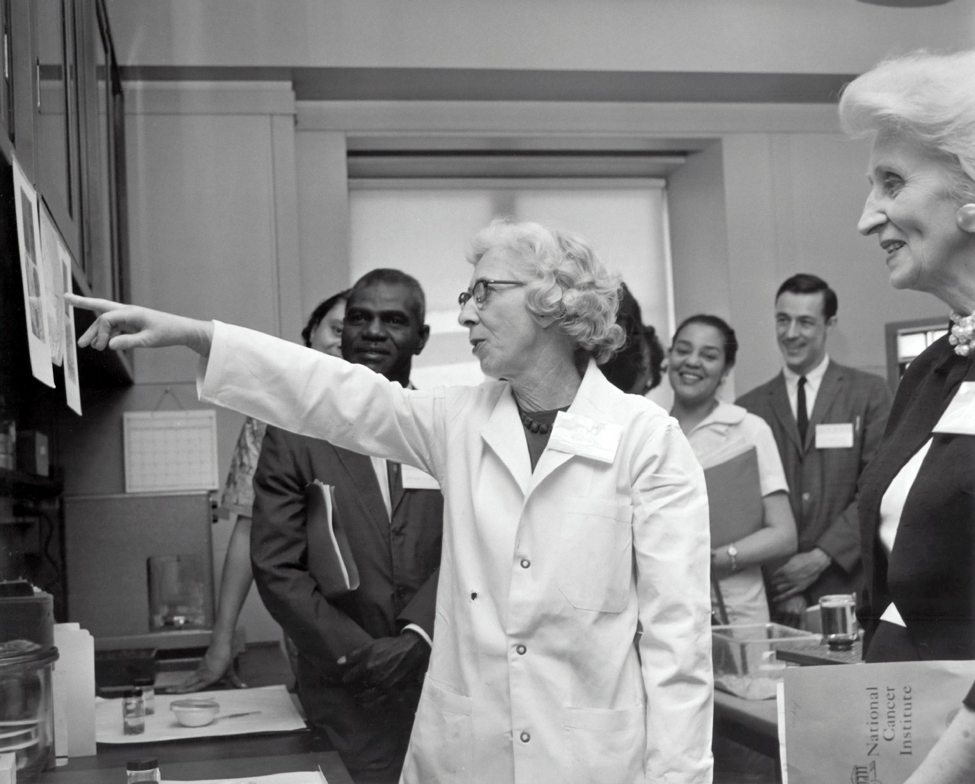 Picture of medical professionals analyzing imaging, with one woman in a white coat pointing to something in the image and showing the others, with a smile on her face and all the other's listening or learning from her.