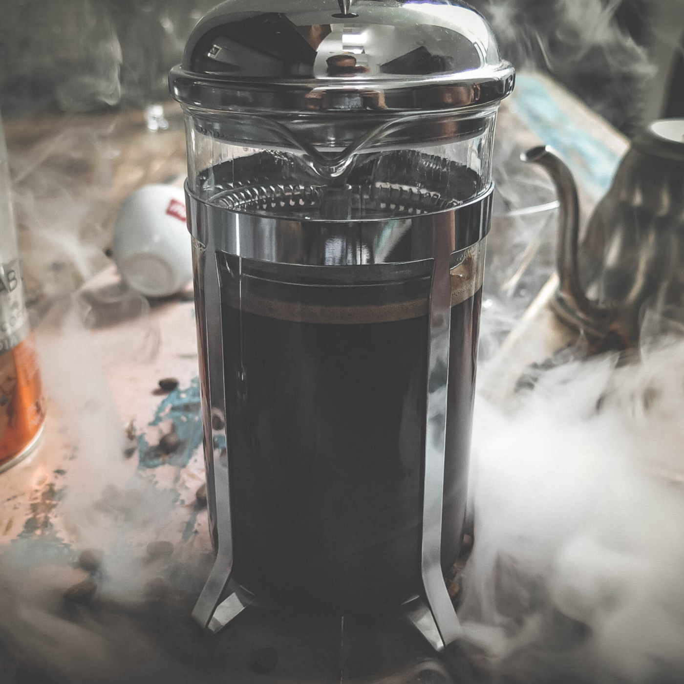 A view of a French press coffee maker with freshly brewed coffee surrounded by hot smoke and other coffee equipment.