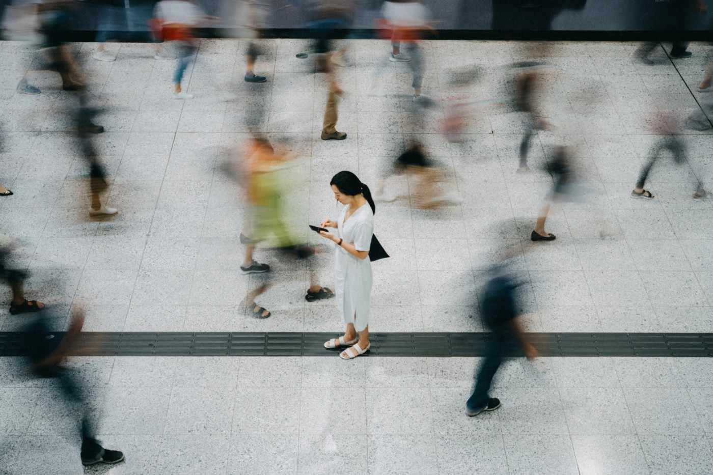 An overhead photo of an Asian woman standing still as blurred people walk by her.