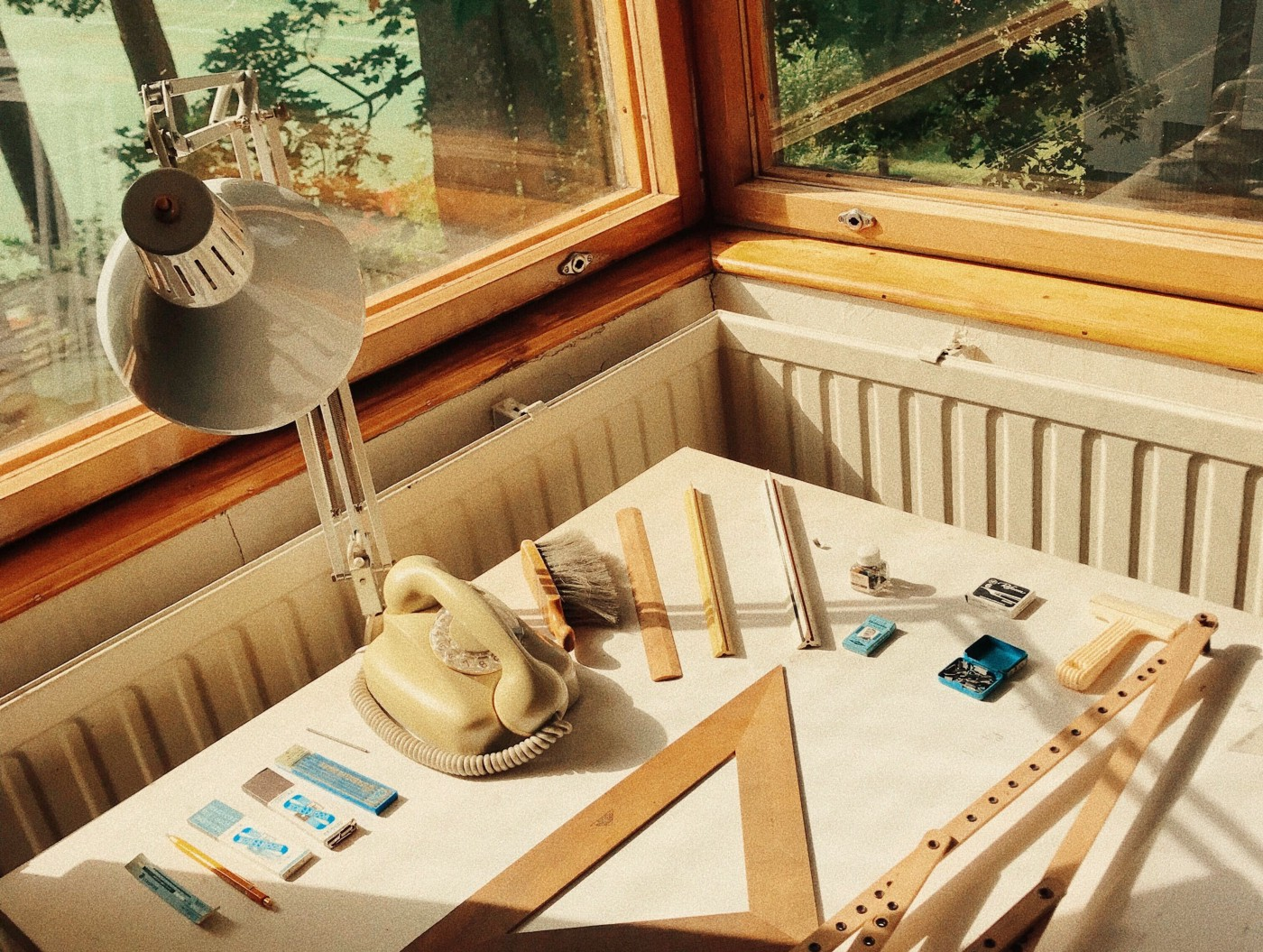 Table, lamp, and the architect's material next to the window