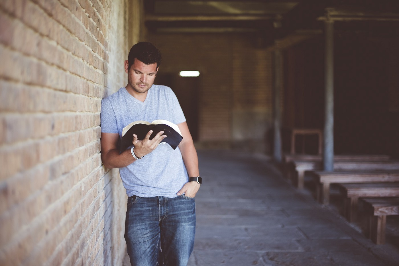 A man leaning on a brick wall reading a book.