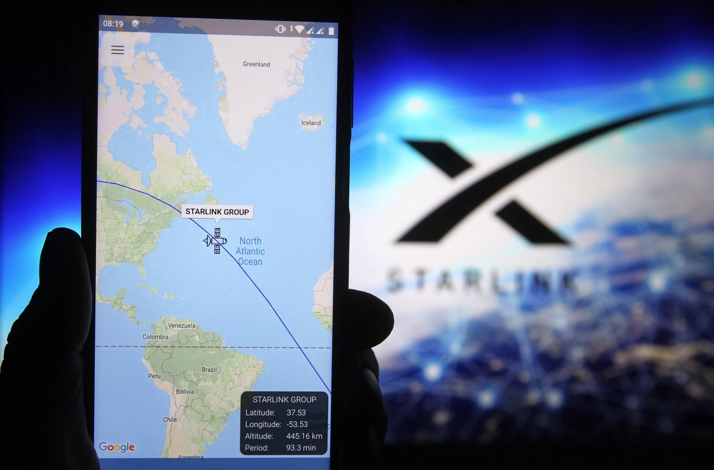 A satellite tracker image is seen displayed on a smartphone with a Starlink logo in the background