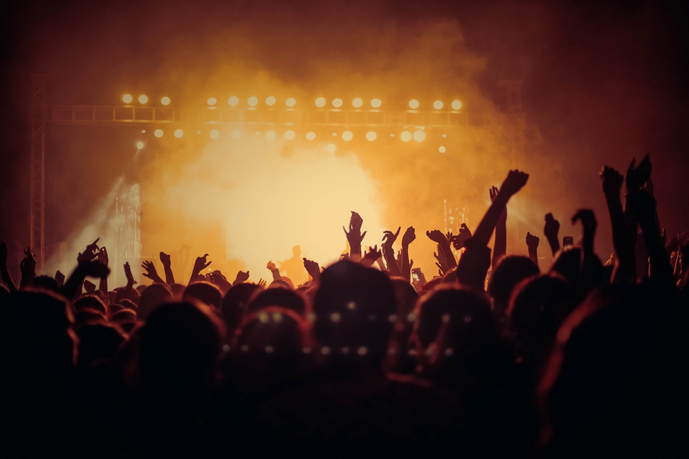 image of a concert with stage lights in background and crowd with hands lifted in silloutette foreground.