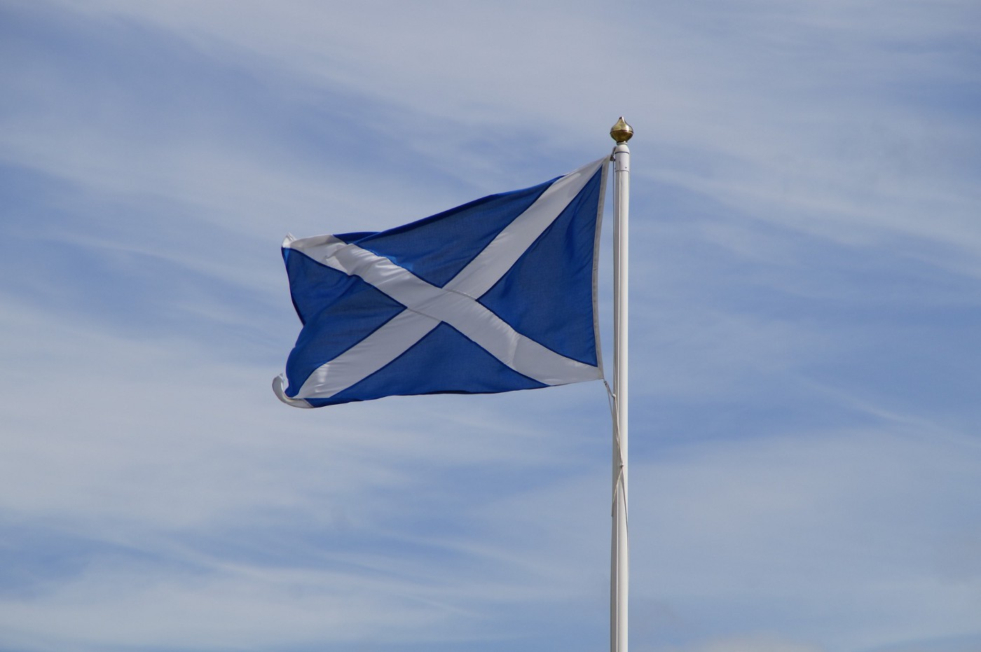 The flag of Scotland waves against a blue sky.