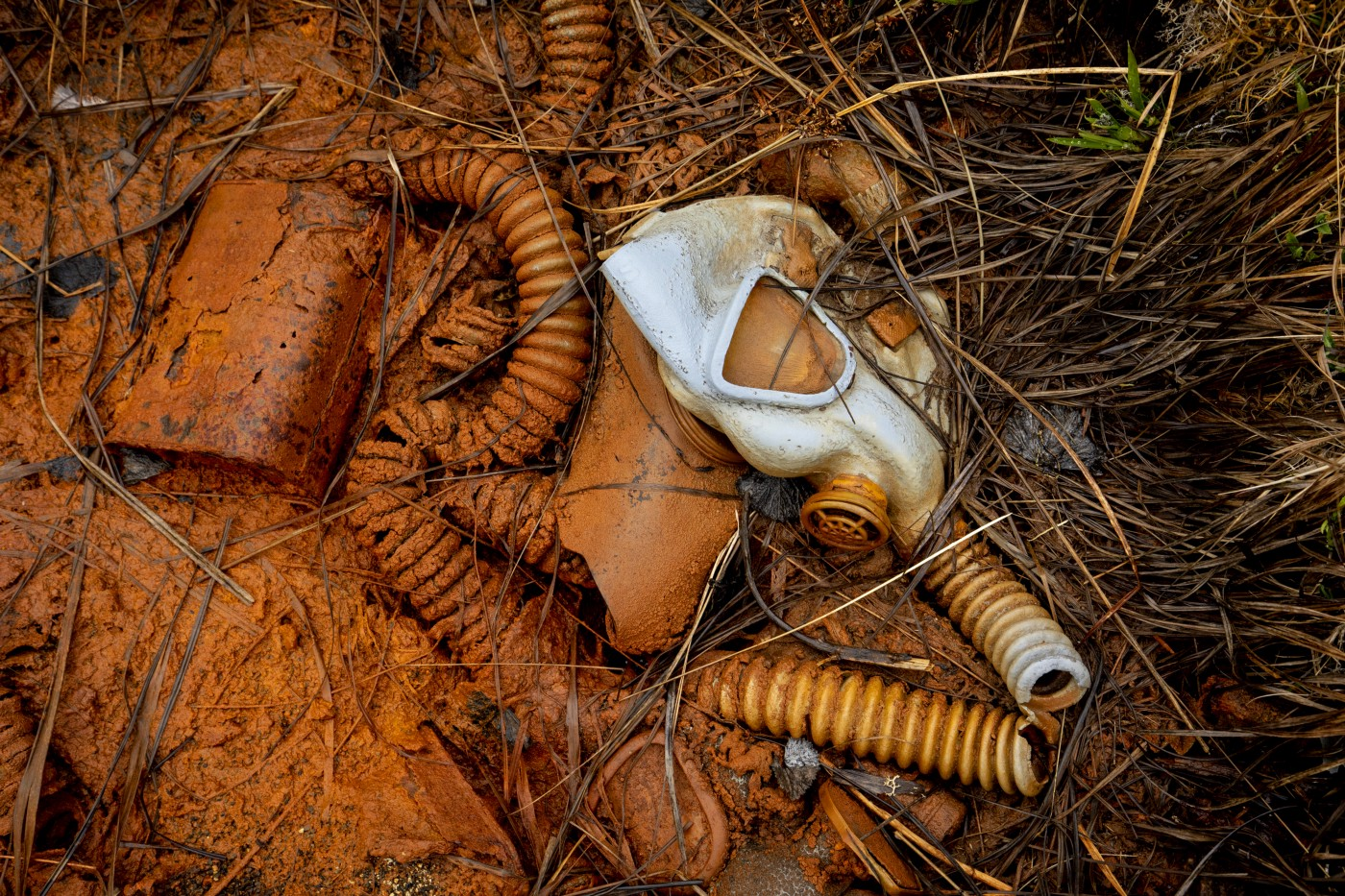 A silver metal face shield lies in rust-colored mud, tubing and other debris is half submerged in the mud, and grass shows at the edges.