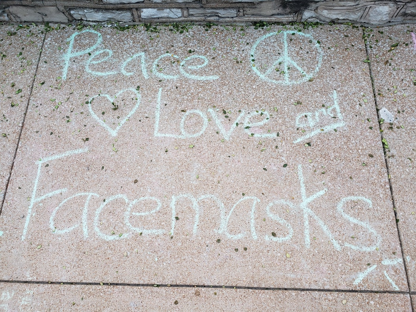 """Sidewalk chalked in light blue """"Peace, Love, and Facemasks"""" outside an elementary school."""