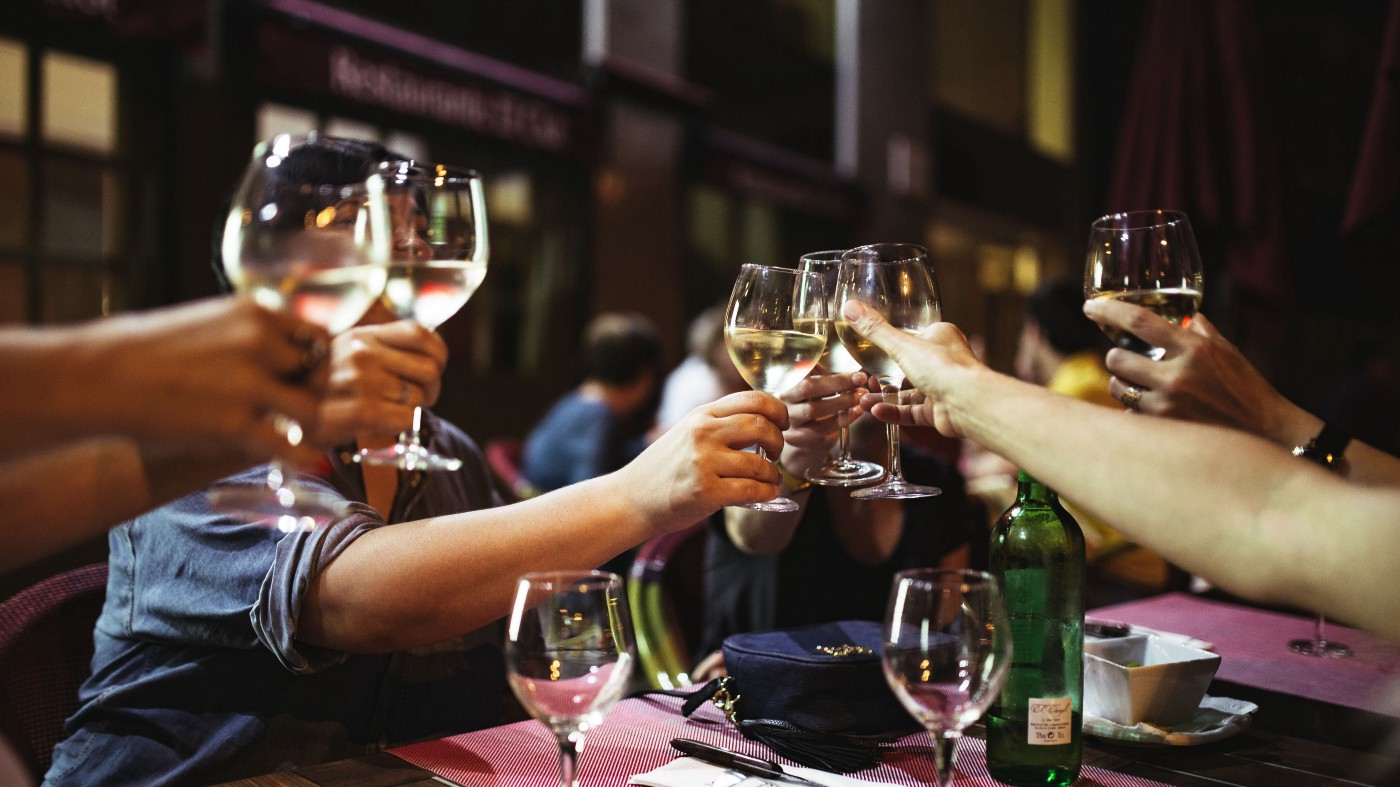 A group of people sat around a dining table, raising wine glasses in a toast.