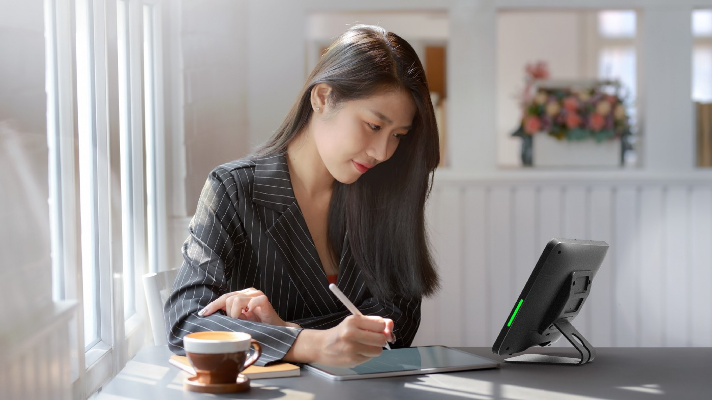 A remote employee works at her desk while conferencing.
