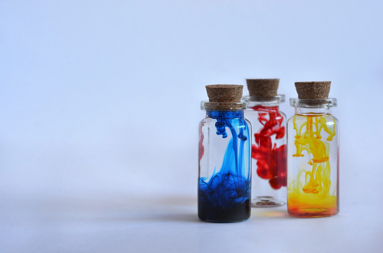 Three small flasks sealed with corks. From left to right: blue, red and yellow dye are being slowly mixed in each one.