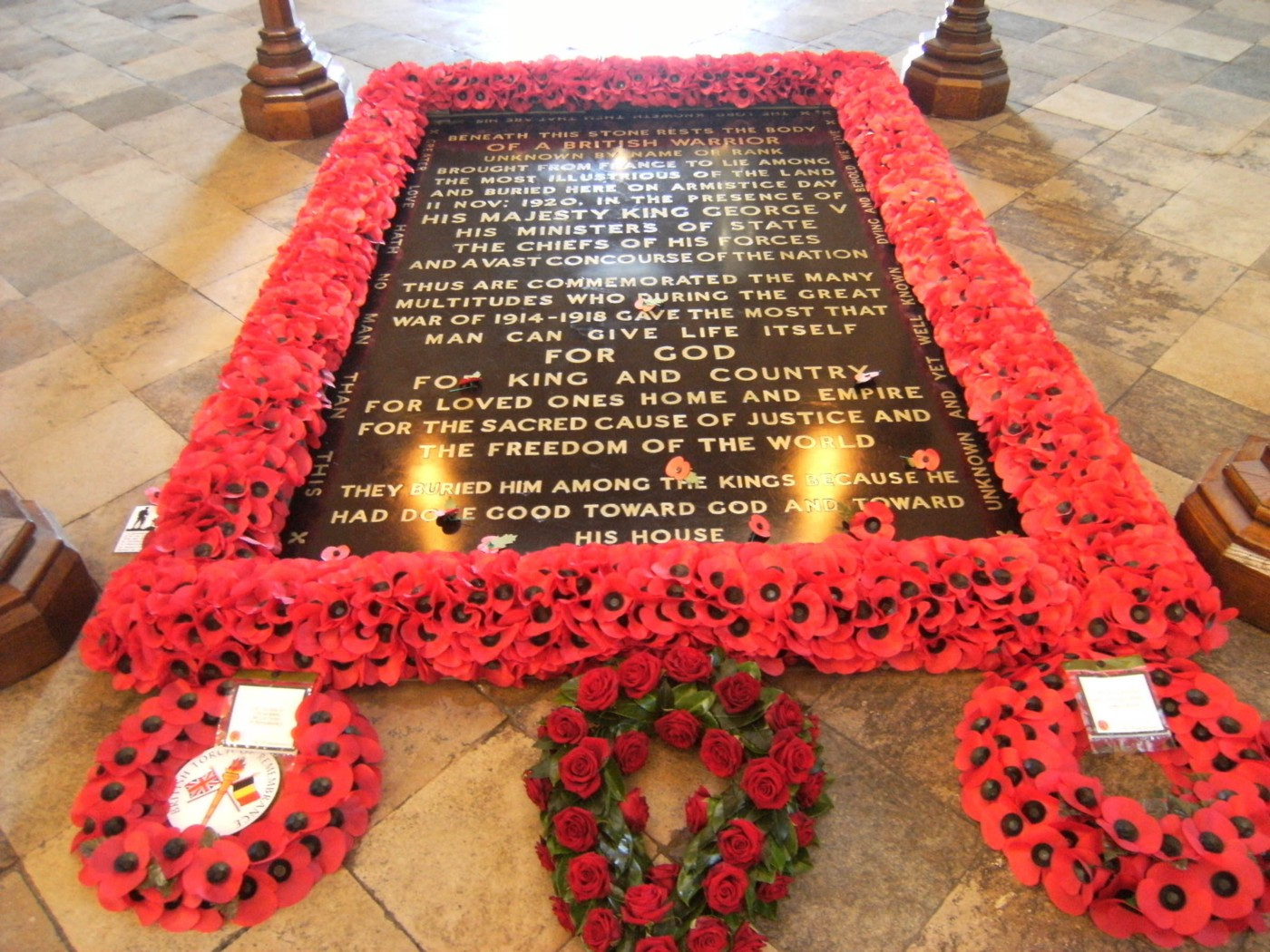 An image of the Tomb of the Unknown Warrior in Westminster Abbey. A black grave set into a tile floor surrounded by poppies and with three poppy wreaths lying in front.