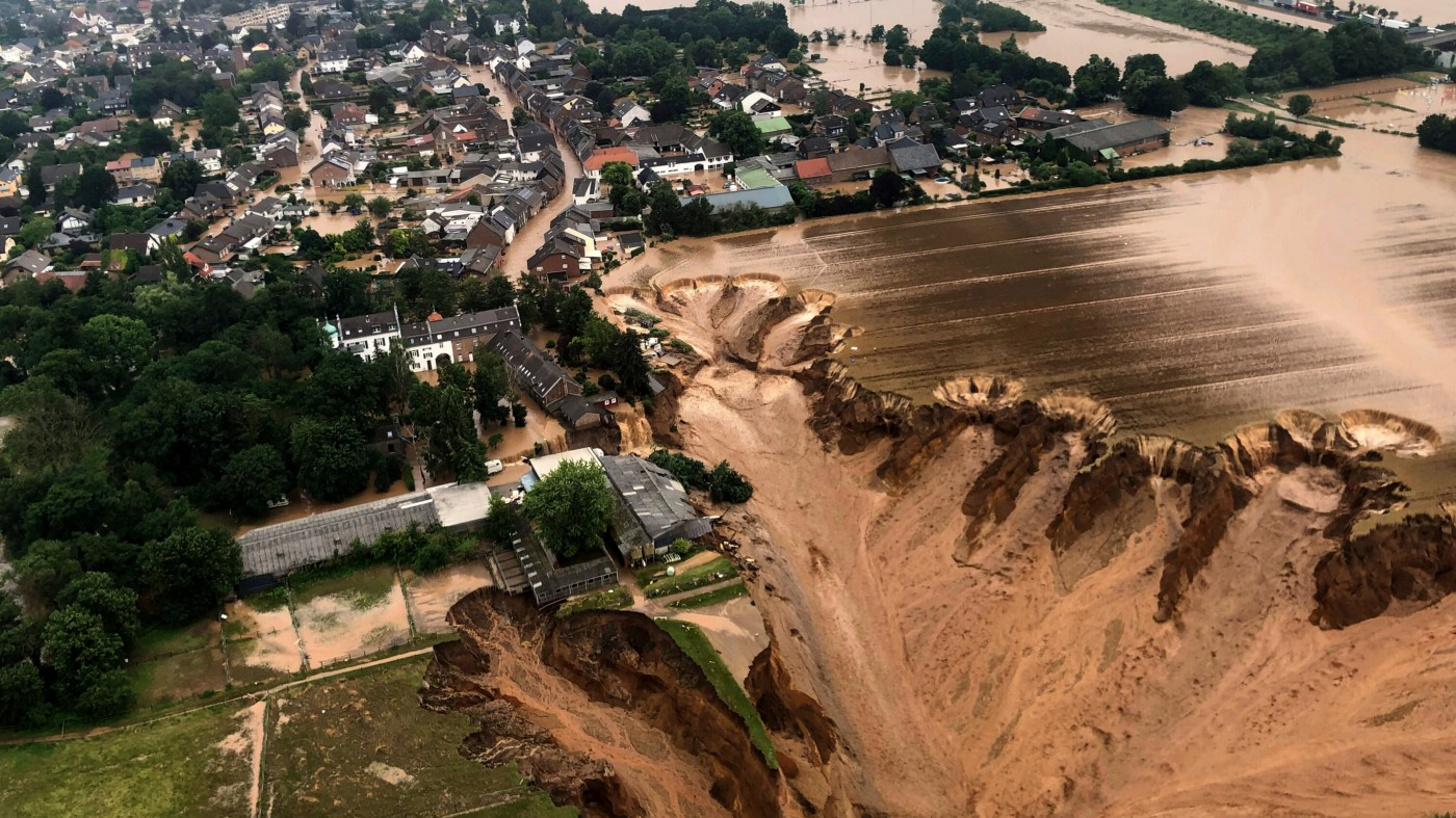 An aerial image of a German town where a quarry dam collapsed from the extreme flooding and a massive sinkhole has swallowed buildings and cars.
