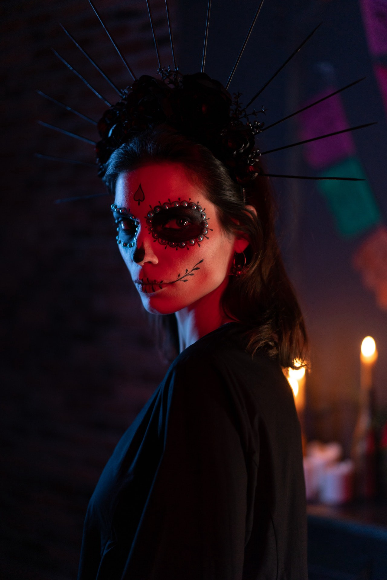 Woman in Mexican skull makeup wearing a black dress in a dimly lit room with candles.