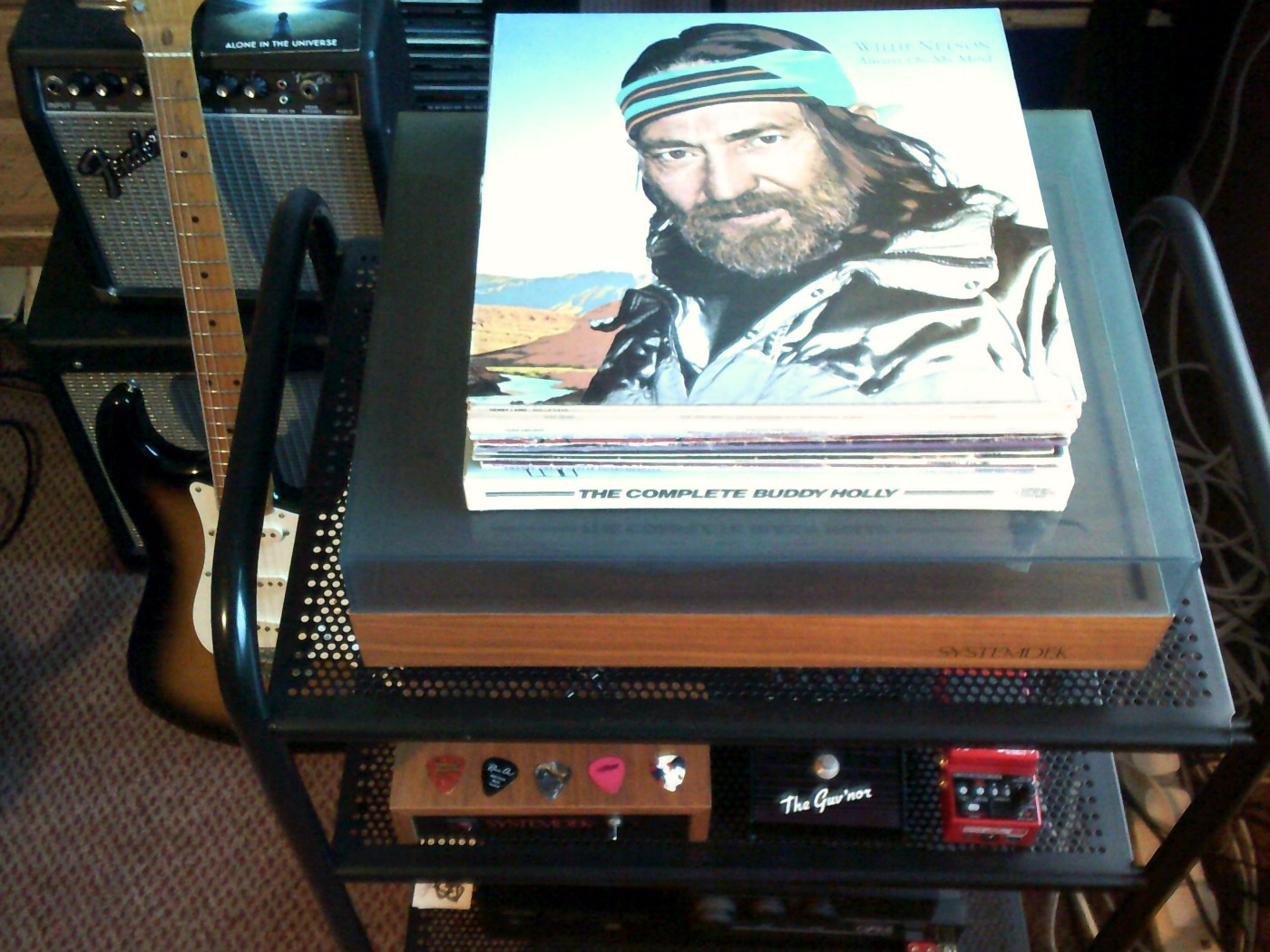 Stack of vinyl long playing records with Willie Nelson's 'A Whiter Shade Of Pale' lying on top of a Hi-Fi System record deck in a music room