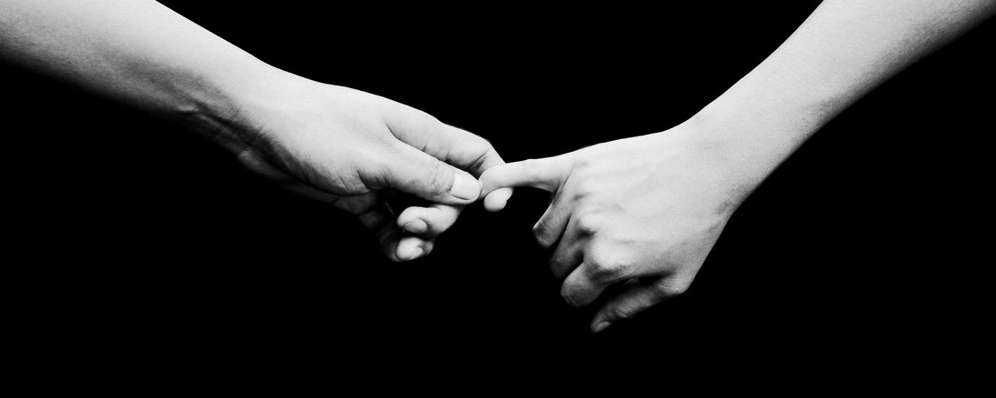 Two hands barely holding on to each other