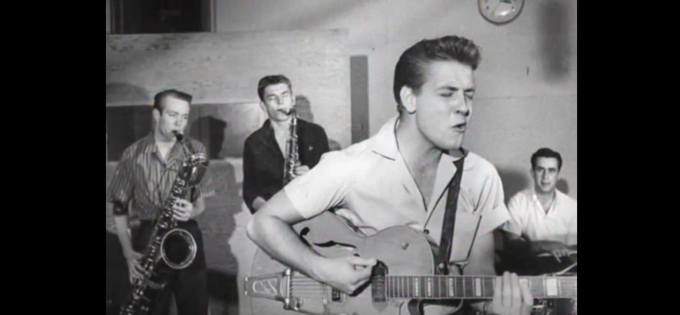 Eddie Cochran playing guitar and singing with two Saxophonists and a drummer behind him.
