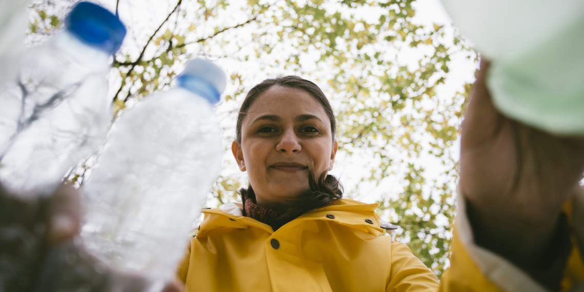 Woman putting plastic bottles in recycle bins