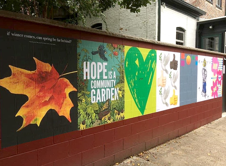 Six posters on the theme of hope are wheat—pasted to a brownish red painted cinderblock wall, with a grey sidewalk in front.