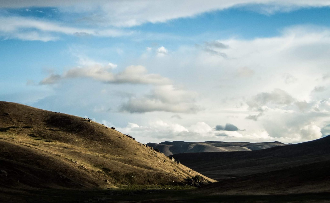 blue sky, white clouds, hills of brown in Mongolia