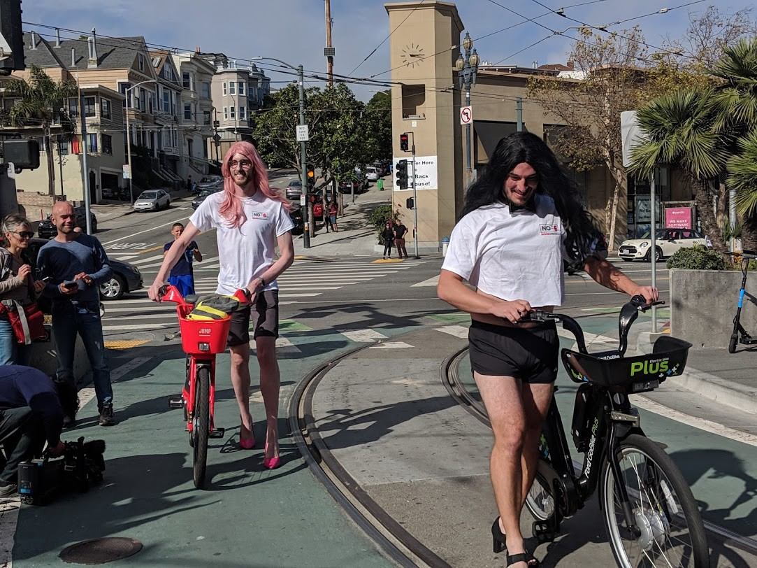 Picture of Scott Wiener in drag with a red bike