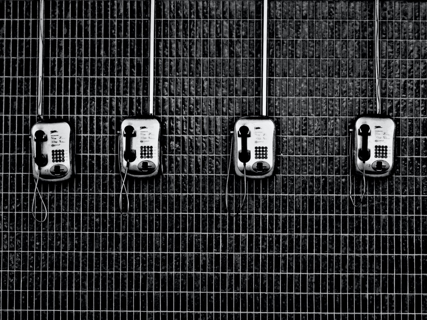Four public telephones on a tiled subway wall.