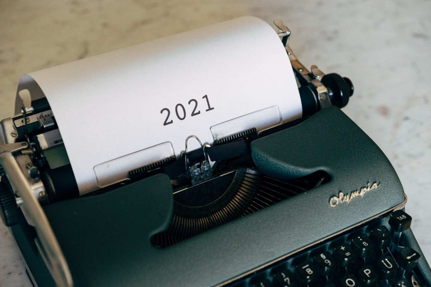an antique typewriter with numbers 2021 on sheet of white paper