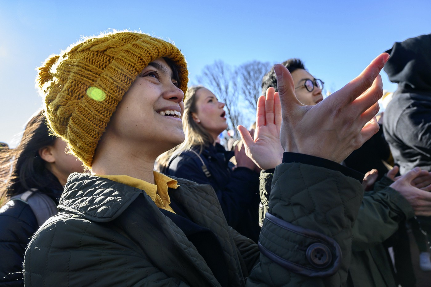 a person in a yellow knit hat, facing right, smiling and clapping, amid a crowd of people
