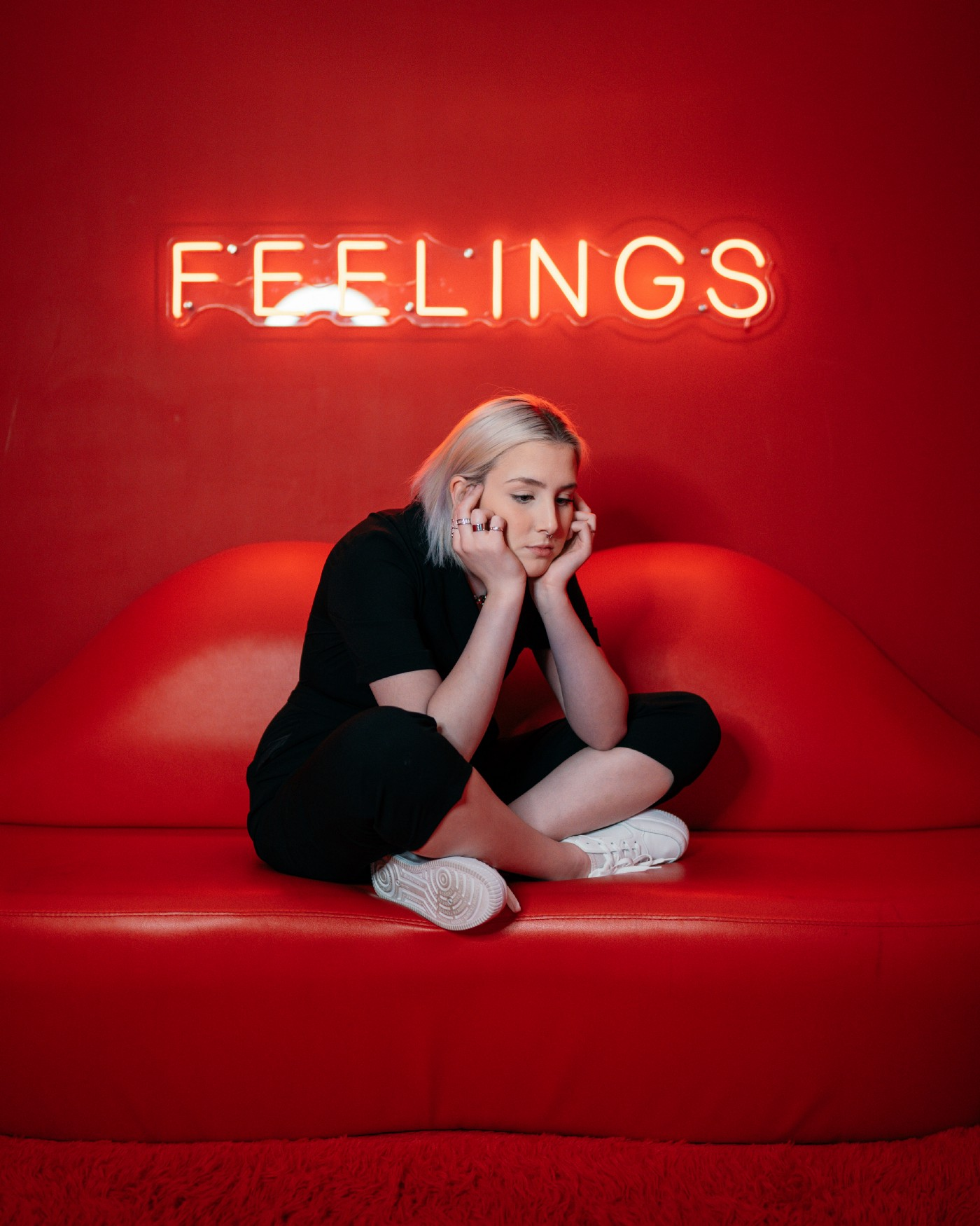 """A woman sits, thinking, on a red couch which is shaped like a pair of lips. There is a neon sign behind her which says """"feelings."""""""