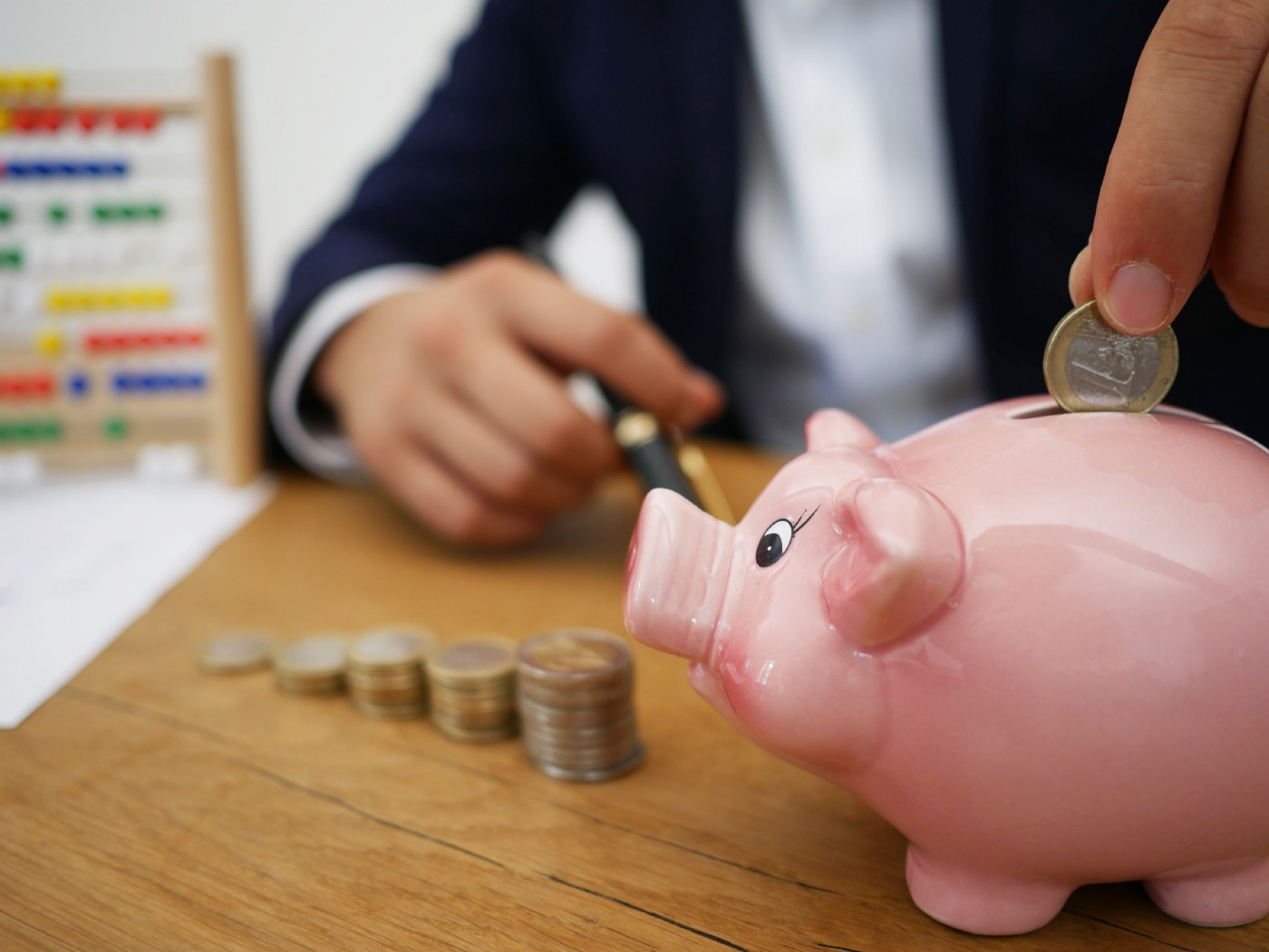 Person inserting coin into piggy bank