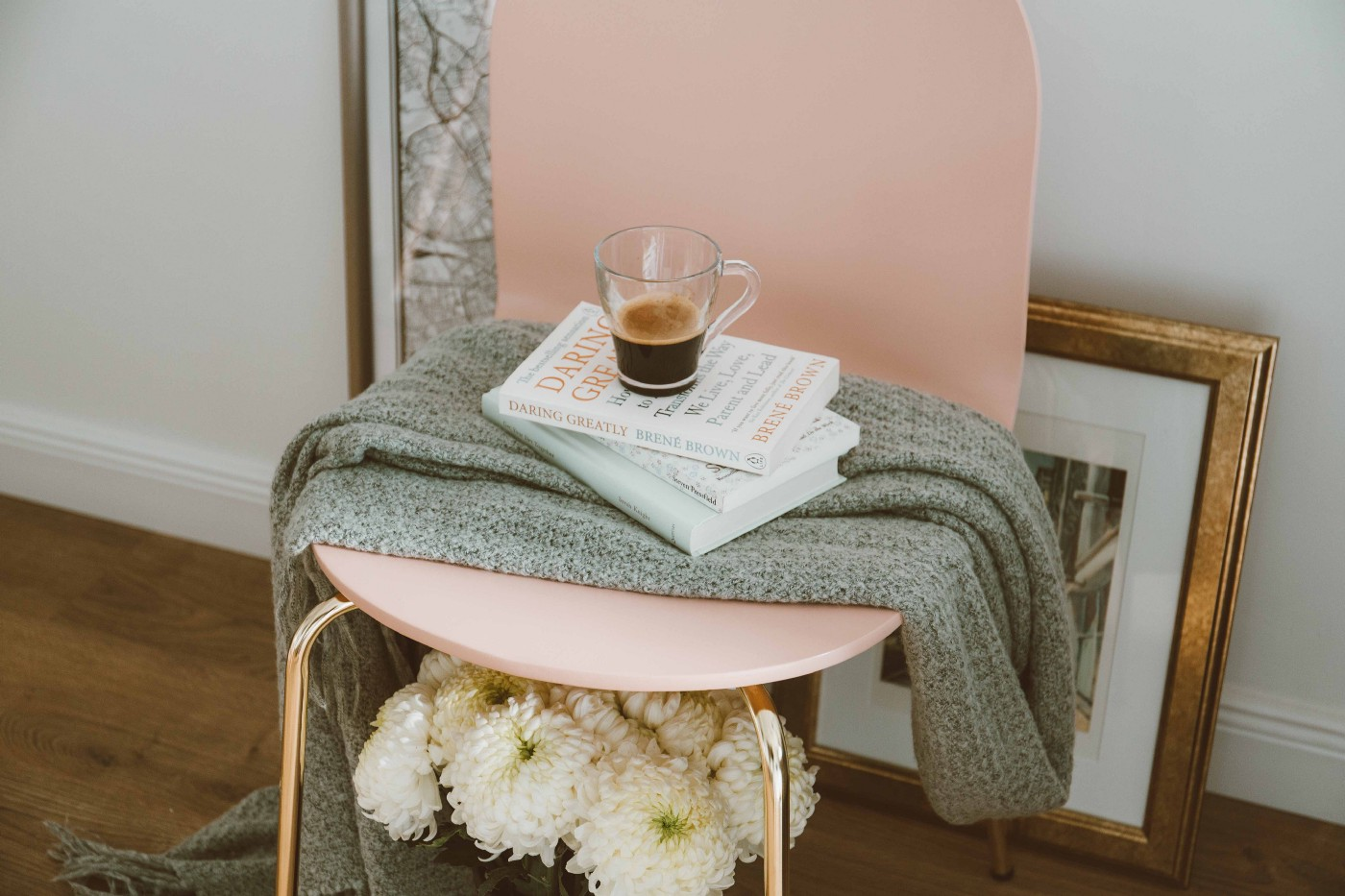 coffee, books, and blanket on chair