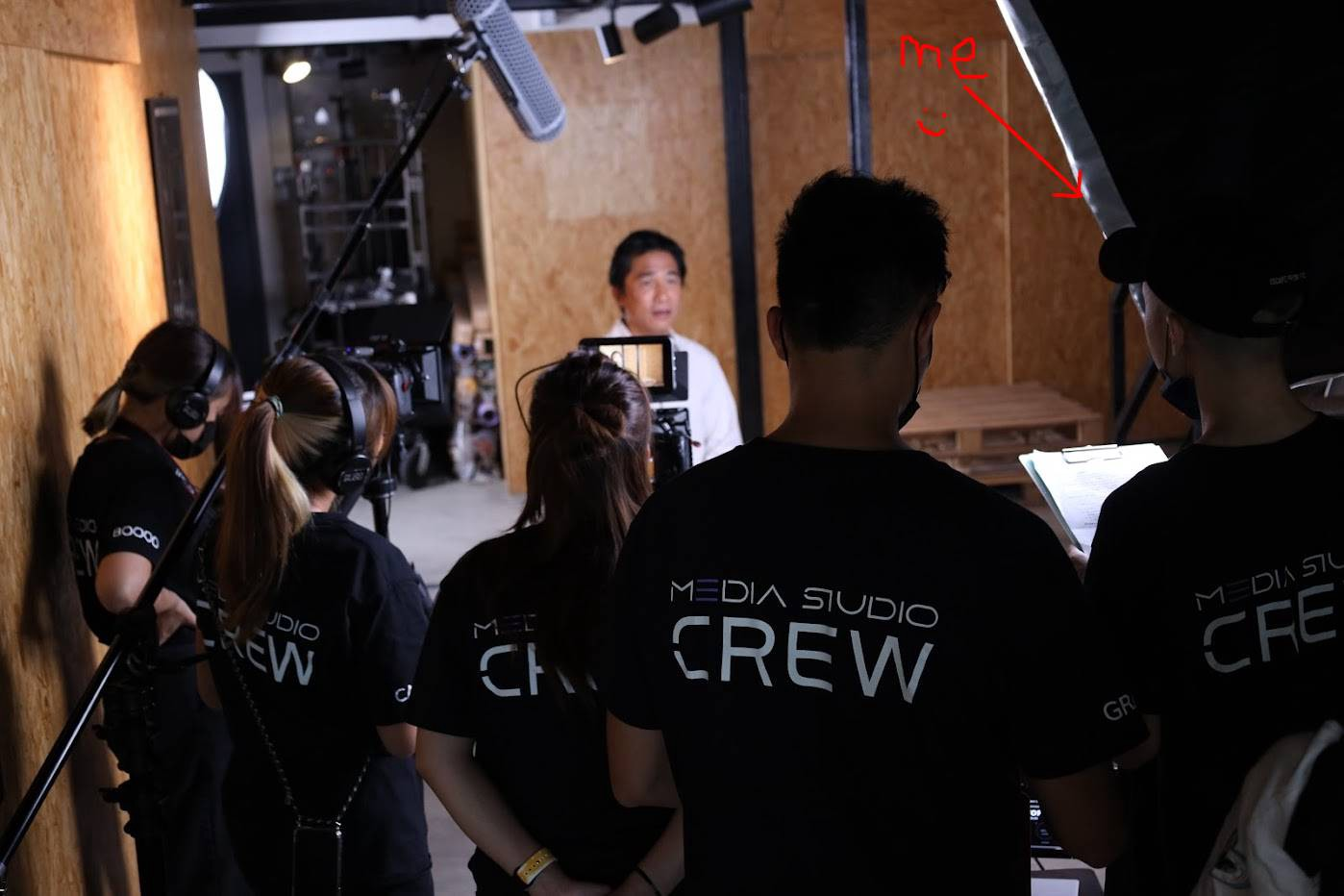 Actor Tony Leung Chiu-wai is in a warehouse. A camera crew of 5 wearing black t-shirts with media studio logo is shooting the interview.