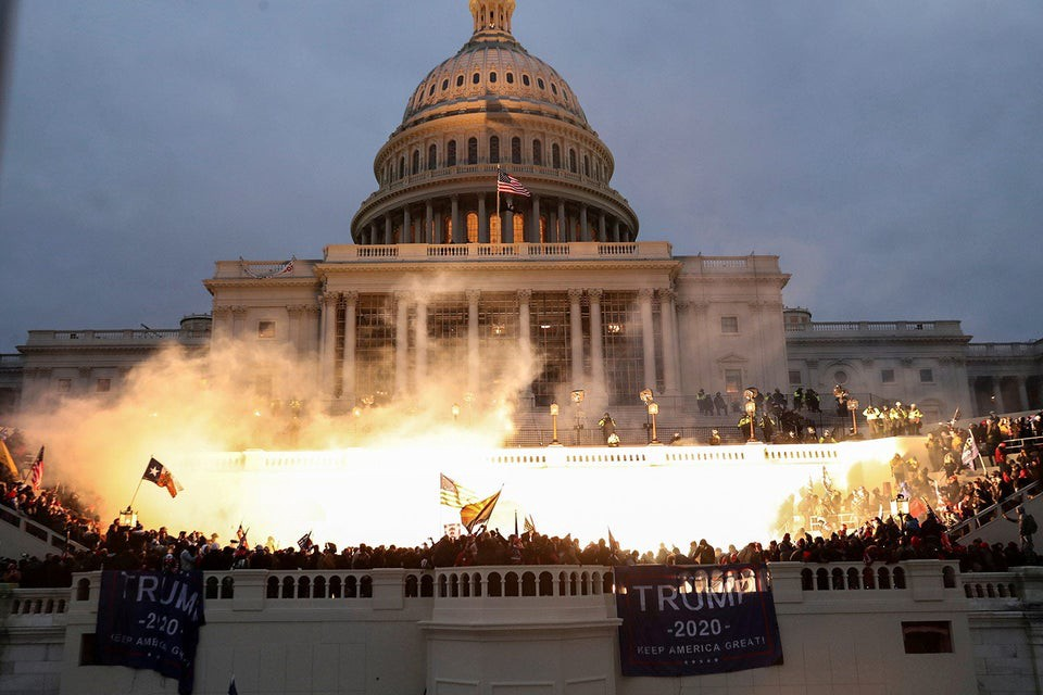 A photo of smoke in front of the U.S. Capitol Building; Trump 2020 flags can be seen hanging in front of a crowd of rioters.