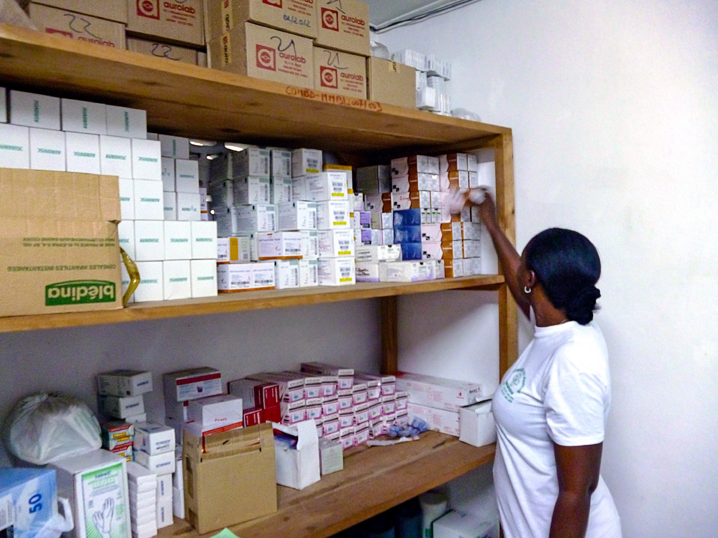 A woman takes a single box of medication from a rack of shelving, full of medicine boxes.