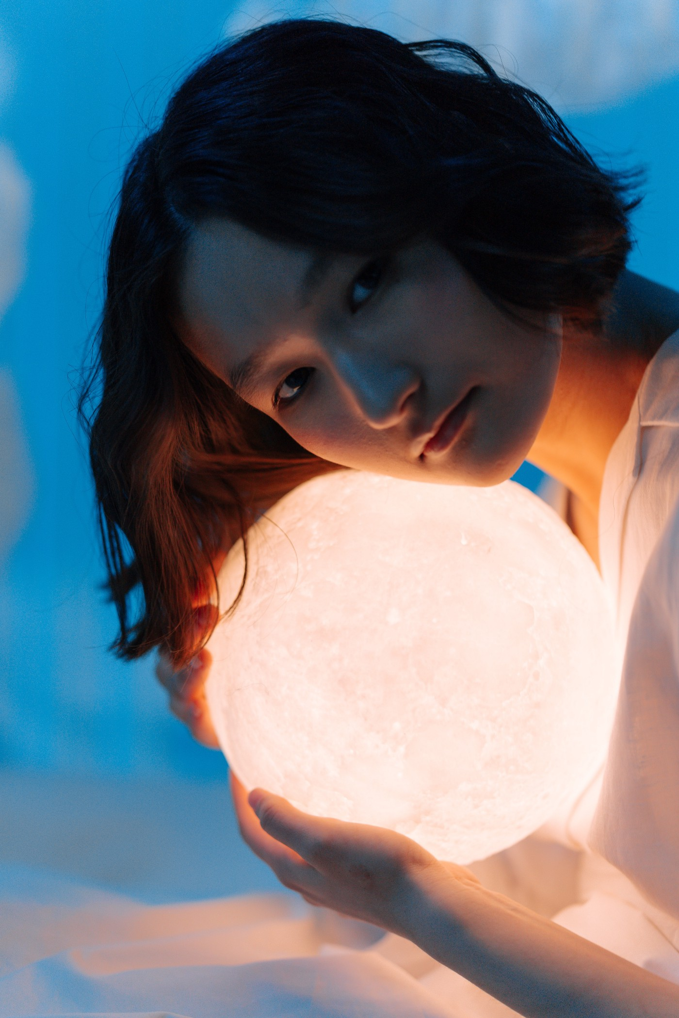 A woman holds a glowing orb under her chin. Moon glow. Calm, reflective feeling.
