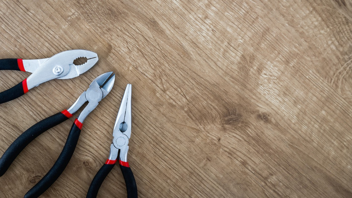 three kinds of pliers lying on a table top