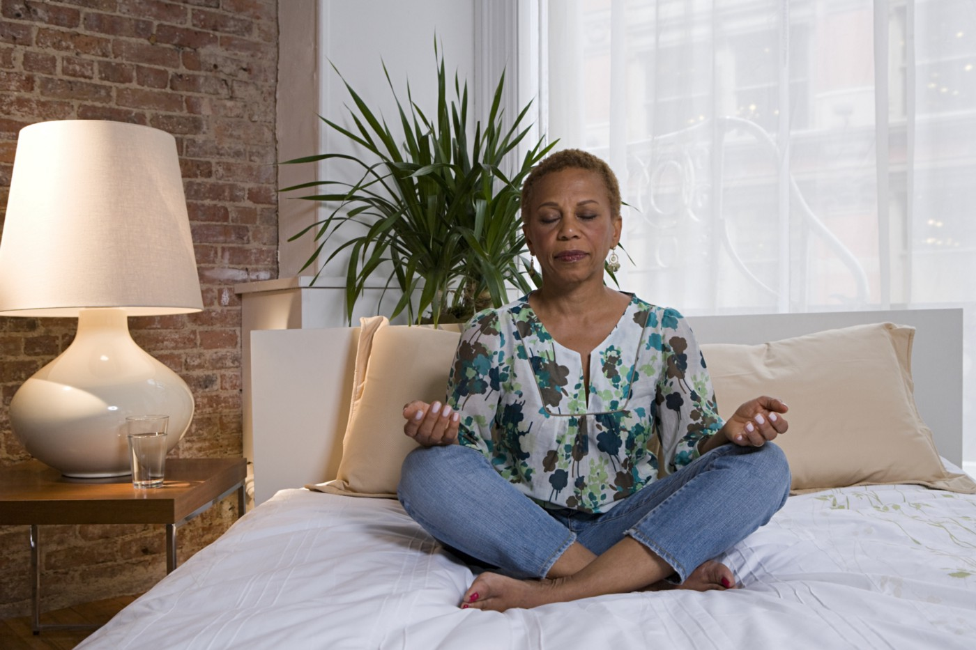 Older Black woman sitting cross-legged meditating on her bed.