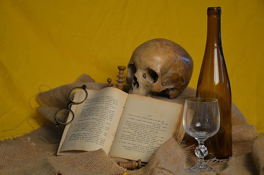 """A """"vanitas"""" photo depicting a skull, an open book, a glass goblet and glass bottle on tan burlap against a gold backdrop."""