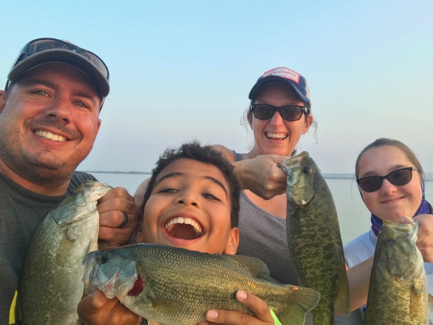 Anglers happily show off their bass catches.