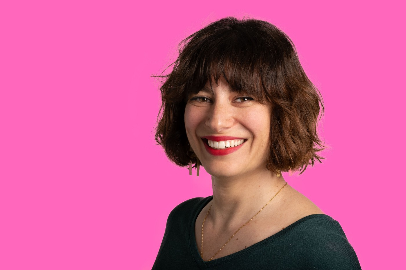 Photo of Anouk against a bright pink background, wearing red lipstick and smiling.