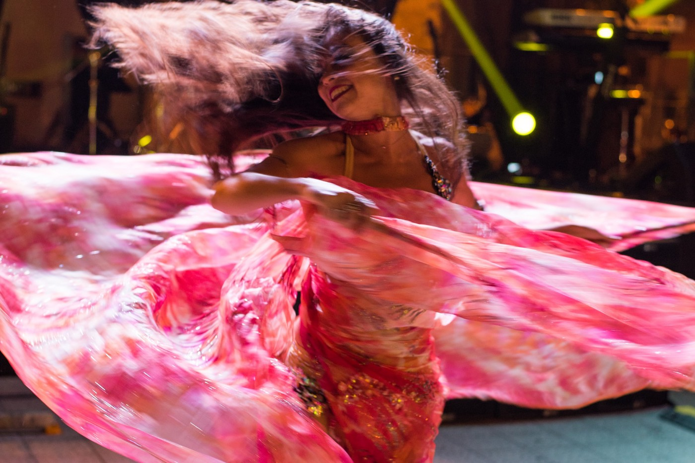Image of a woman belly dancing/twirling in a pink dress